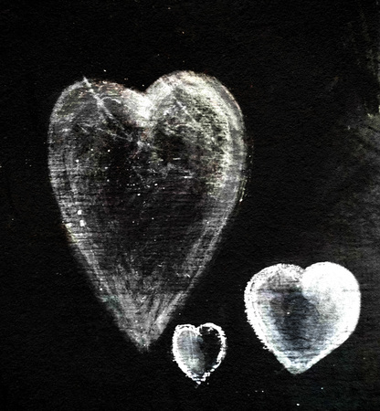 Three chalk hearts of different sizes on a piece of dark gray slate, smudged chalk on rough slate texture. Фото со стока