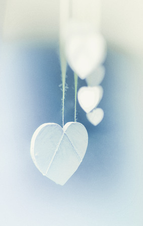 Hanging heart shapes, a row of small white hearts hanging on rough threads, viewed from the end, vignette blur, blue and yellow tints.