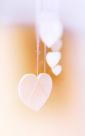 Hanging heart shapes, a row of small white hearts hanging on rough threads, viewed from the end, vignette blur, orange and purple tints.