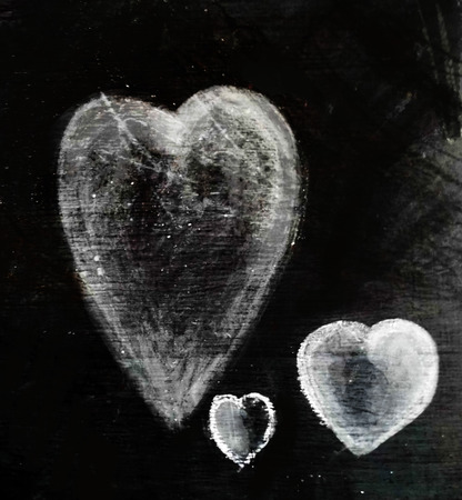 Three chalk hearts of different sizes on a piece of dark gray slate, smudged chalk on rough slate texture. Stock Photo