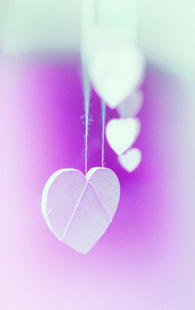 Hanging heart shapes, a row of small white hearts hanging on rough threads, viewed from the end, vignette blur, magenta and green tints.