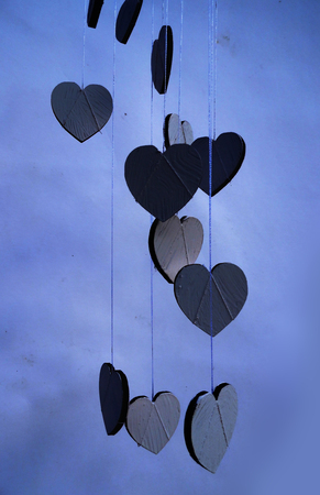 Hanging heart shapes, a group of small hearts hanging at different heights on rough threads, blue tints. Banco de Imagens