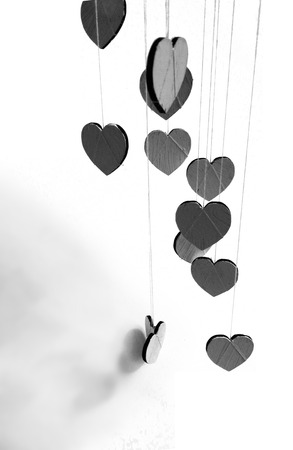 Hanging heart shapes, top-down angled view a group of small hearts hanging at different heights on rough threads, with shadows, grays.