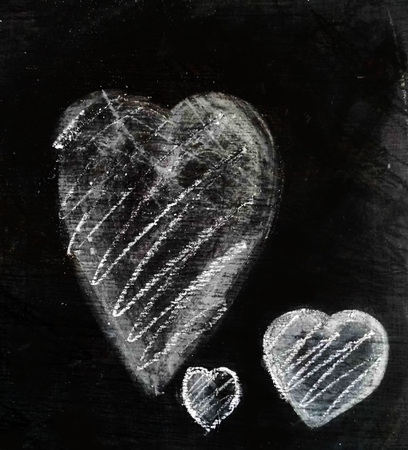 Three chalk hearts of different sizes on a piece of dark gray slate, smudged chalk on rough slate texture, with additional rough hatching.