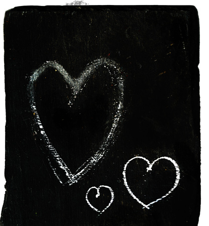 Three chalk heart shaped outlines of different sizes on a piece of dark gray slate.