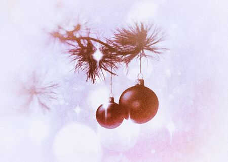 Christmas card with pine boughs and baubles on a background with star shapes and bokeh, red and purple tints and vignette blur.