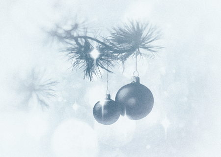 Christmas card with pine boughs and baubles on a background with star shapes and bokeh, blue tints and vignette blur.
