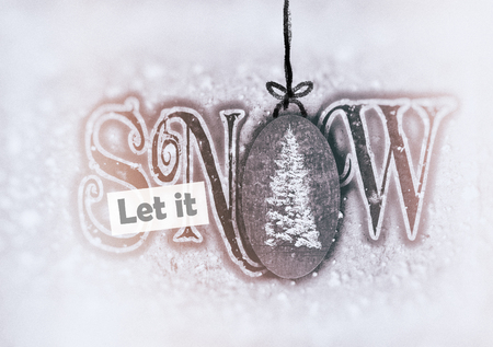 Christmas card with the words Let it snow, in contemporary fonts, with images of snow and fir tree, with vignette blur.