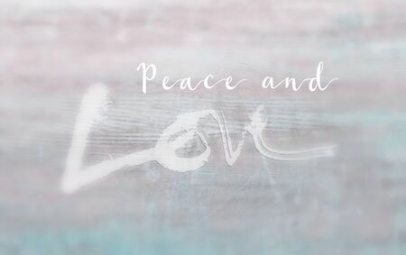 Christmas card with the words Peace and Love, with the Love lettering rough sketch painted style on painted texture background, vignette blur, blue and pink tints.