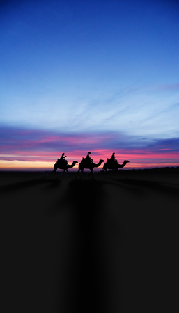 Three Kings Christmas card with the 3 wise men on camels on a simple desert landscape with shadows 3D image, with a real sunset, tall.