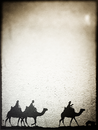 Three Kings Christmas card, design style with silhouettes of the 3 wise men on camels on a rough surface with a single star over a distant barn, with frame effect, rough stone texture and blur vignette, brown tints.