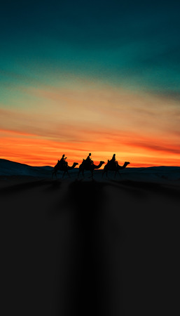 Three Kings Christmas card with the 3 wise men on camels on a simple desert landscape with shadows 3D image, with a real sunset, orange and blue tints, tall. Foto de archivo