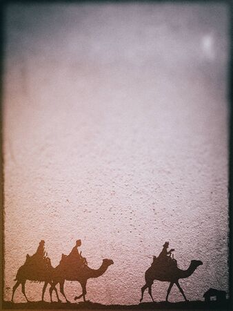 Three Kings Christmas card, design style with silhouettes of the 3 wise men on camels on a rough surface with a single star over a distant barn, with frame effect, with rough stone texture and blur vignette.