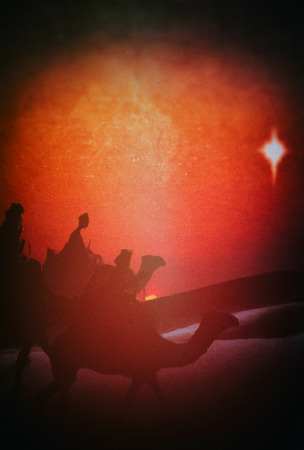 Three Kings Christmas card with silhouettes of the 3 wise men on camels in a desert landscape with sand dunes, a misty sunset following a single star, with slight sketch painted texture and a dark blur vignette, red tints.