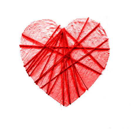 Small white-painted wooden heart shape wrapped with red threads, isolated on a white background, red tinted.
