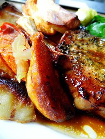 Roast pork dinner with meat and vegetables, on a plate on a table, closeup. Stock Photo