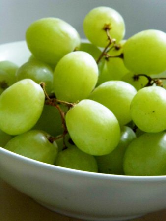 White grapes in a small ceramic bowl, with water drops.