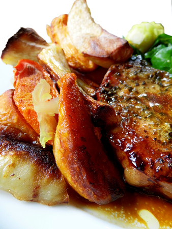Roast pork dinner with meat and vegetables, on a plate on a table, closeup. Banco de Imagens
