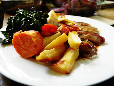 Roast lamb with vegetables on a plate on a table. Banco de Imagens - 121929338