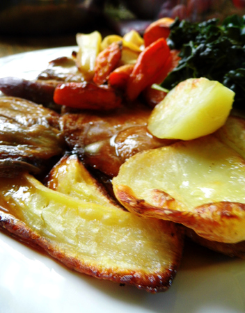 Roast lamb with vegetables on a plate on a table.