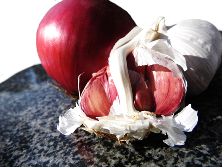 Red onion and garlic on a chopping board.