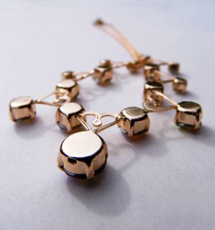 Gold bracelet closeup, on a flat surface.