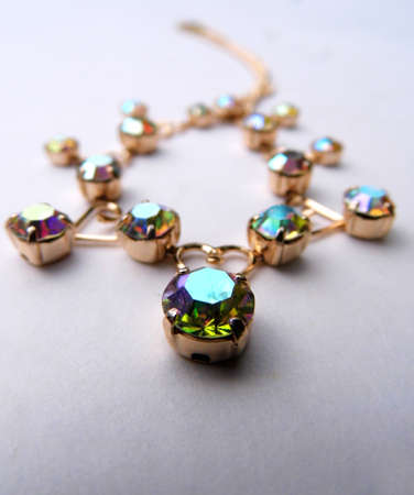 Gold bracelet with colored glass closeup, on a flat surface.
