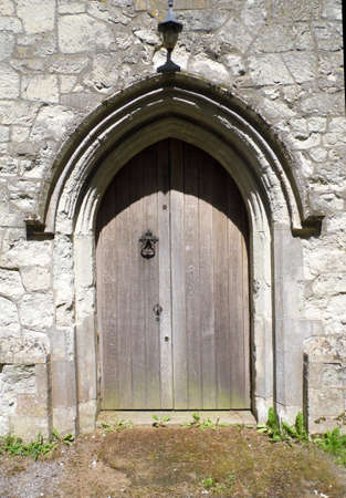 An old church doorway in the sun, with wood and pale stone, with a pointed arch. Banco de Imagens