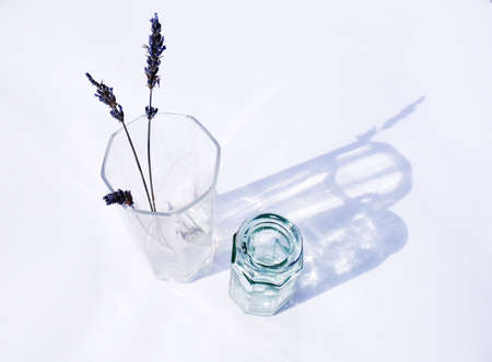 Dried lavender in a sunlit glass vase with a smaller vase beside.