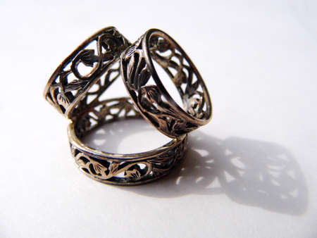 Silver scarf ring on a flat surface with shadow.