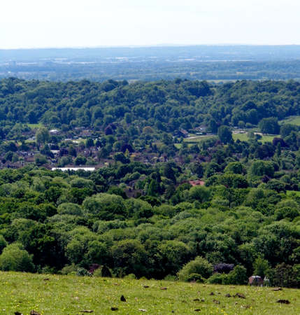 British summer landscape, from a hill, with fields, farms and forests, Surrey, UK.