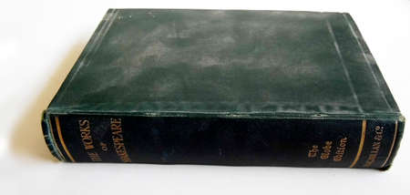 Old book with a dark cover lying on a surface, lit from the side with shadow.