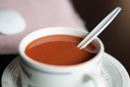Tomato soup in mug with spoon and seasonings from angle