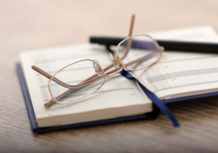 Note-book, glasses and a pen on a wooden table