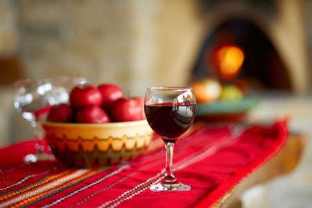 Glass of red wine on a table, behind a fireplace Stock Photo