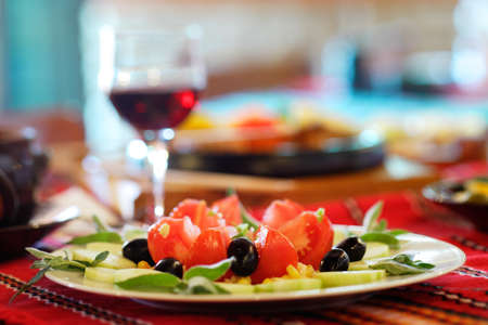 Greek salad with tomato, cucumbers and black olives, a glass of red wine in the background Stock Photo