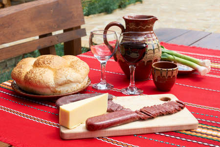 Traditional Bulgarian food wine, sassage and yellow cheese on rural table