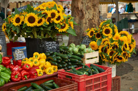 sales person: Fresh vegetables and sunflower blossoms for sale at farmers market in Aiv en Provence, France