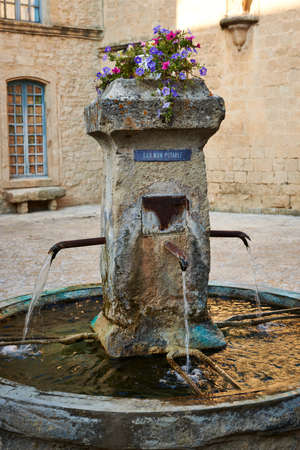 Ancient fountain on the central square of Grambois village, Provence, South France