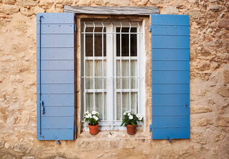White Provence window with blue covers and pots of flowers in Grambois village, South France