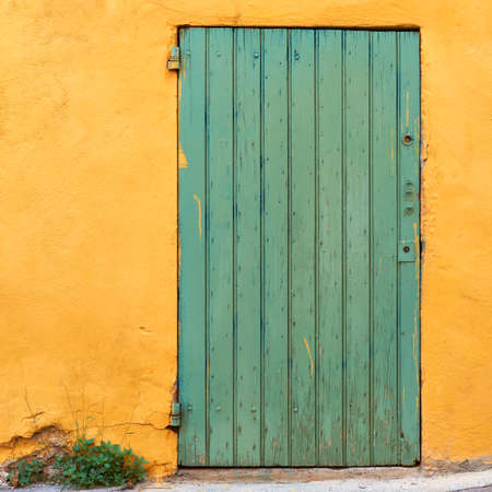 Green door on yellow wall in French village, typical colors of Provence