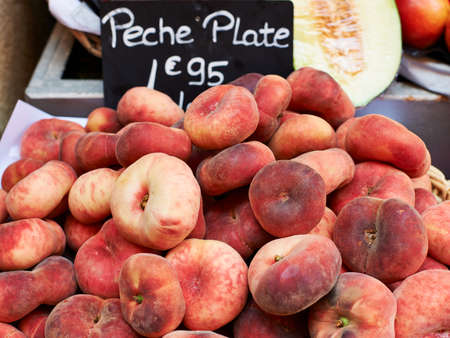 Red ripe flat peaches for sale on market stall in Provence, South France