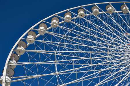 Part of very large ferris wheel against blue sky Stock Photo