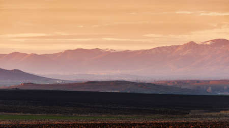 Winter landscape with mountain and ploughed land at sunset light Stock Photo