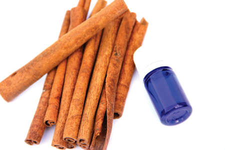 cinnamomum: Cinnamon essential oil bottle and sticks