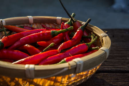 Red dry chilli in bamboo basket on old wood background