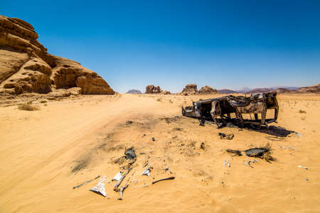 pices: Burnt car in the middle of nowhere in Wadi Rum desert in Jordan. Looks like the car rolled or was flipped by the power of explosion that might have took place. Ashes and pices of tires were found all around the car.