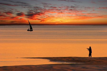 Beach sunset scene in Mozambique with fisherman and small sailboat (called a dhow) Stock Photo