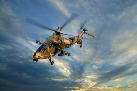 Een gecamoufleerd militaire helikopter tijdens de vlucht tegen een dramatische hemel