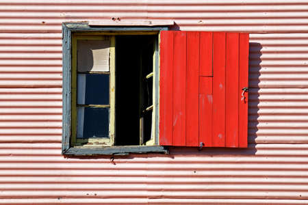Old window with coloful red shutter in La Boca, Buenos Aires, Argentina photo